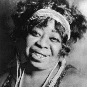 circa 1923: Portrait of American blues singer Ma Rainey (1886-1939), smiling, wearing a headband, beaded necklace, and a sequined dress. (Photo by Frank Driggs Collection/Getty Images)